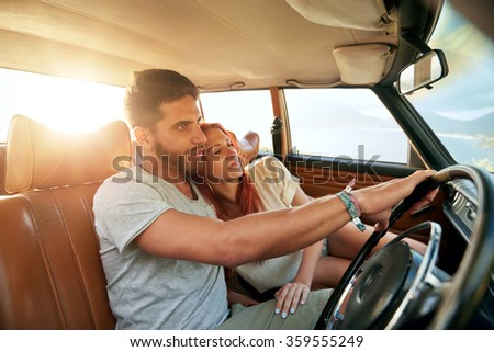 Romantic young couple in their car going on a road trip. Young man driving car with woman sitting by on a summer day. - stock photo