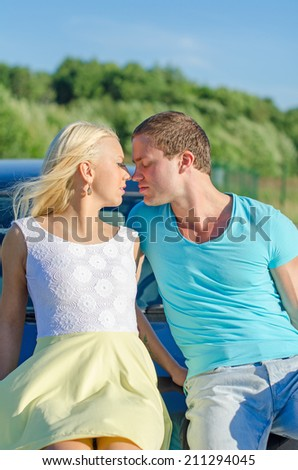 Romantic young couple kissing on the car's hood. - stock photo