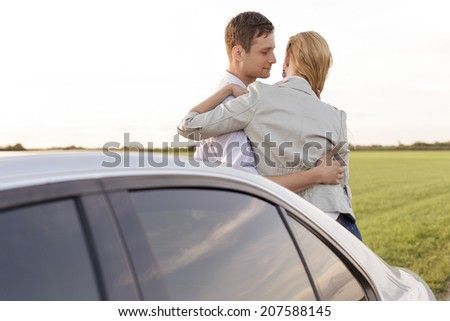 Romantic young couple leaning on car during road trip - stock photo