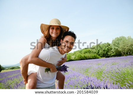 romantic young couple man and woman in summer holiday having fun lavender field provence south France - stock photo