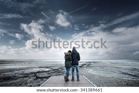 Romantic young couple on a pier looking away, back view, lake and mountains on background - stock photo