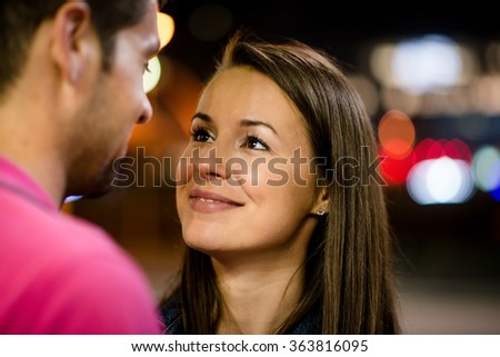 Romantic young couple on date in street at night looking to their eyes