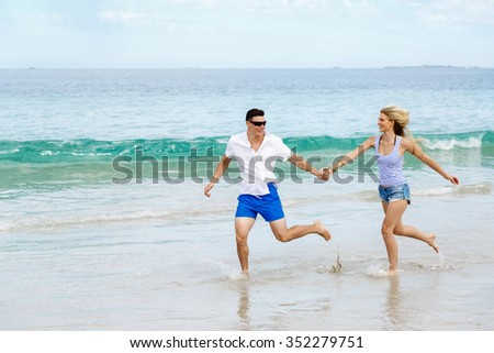 Romantic young couple on the beach running along the shore