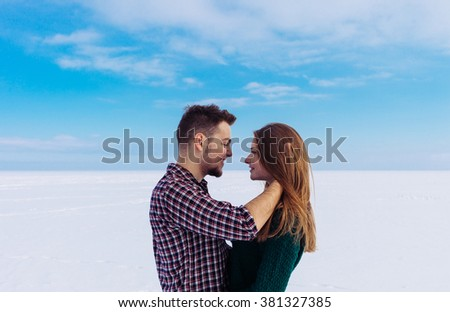 Romantic young couple on the snowy white river surface under beautiful blue sky.