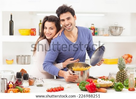 Romantic young couple preparing pasta at home. - stock photo