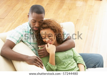 Romantic Young Couple Relaxing Sitting On Sofa - stock photo