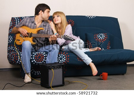 Romantic young couple resting on a sofa with a music - stock photo