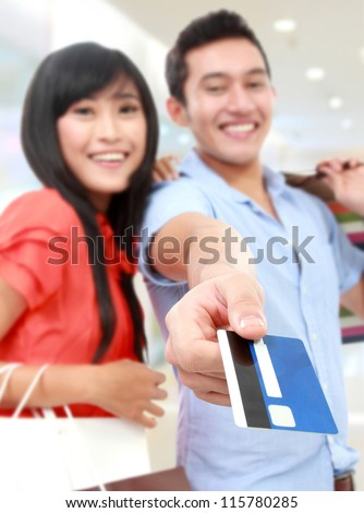 Romantic young couple shopping at the mall and paying using credit card - stock photo
