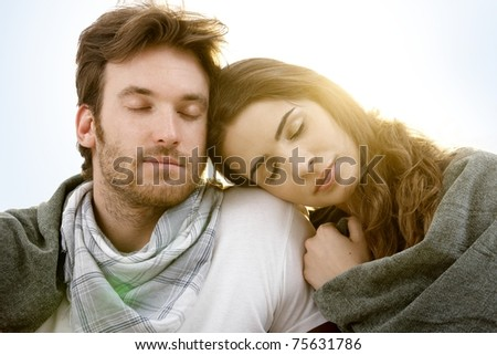 Romantic young couple sitting and resting with closed eyes in summer sunshine.? - stock photo