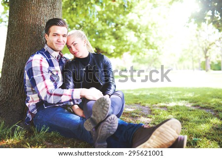 Romantic Young Couple Sitting Beside a Tall Tree at the Park and Smiling at the Camera on a Very Sunny Day. - stock photo