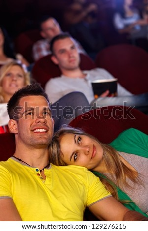 Romantic young couple sitting in cinema, watching movie, smiling. - stock photo