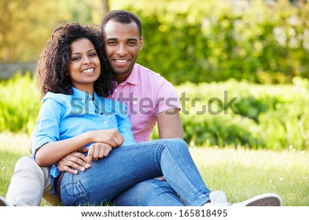 Romantic Young Couple Sitting In Garden - stock photo
