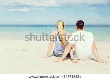 Romantic young couple sitting on the beach looking at the ocean - stock photo