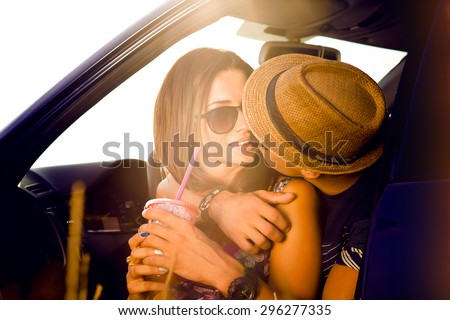 Romantic young couple sitting on the hood of their car while out on a roadtrip.Beautiful young woman kissing her boyfriend looking away smiling,outdoors.Car alongside coastal seashore bright sunlight - stock photo