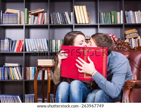 Romantic young couple sneaking a kiss as they sit reading in a library holding up a large red book to partially conceal their faces - stock photo