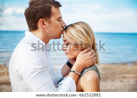 Romantic young couple standing head to head at beach.Romantic young couple together outdoors.