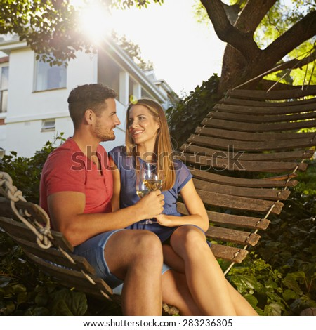 Romantic young couple toasting wine while sitting on a hammock in backyard. They are looking at each other smiling and drinking wine. Young man and woman together caught in a romantic moment. - stock photo