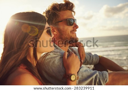 Romantic young couple together outdoors on a summer day. Caucasian couple enjoying the beach view. - stock photo