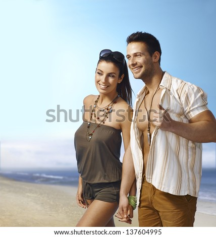 Romantic young couple walking on the beach hand in hand, smiling happy. - stock photo