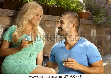 Romantic young couple with drinks in the garden, glasses of whiskey, looking at each other, smiling. - stock photo
