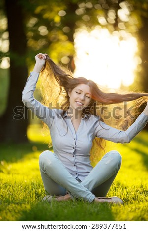 Romantic young girl outdoors enjoying nature Beautiful Model in Casual jeans in light Long healthy Hair  Backlit Warm Color Tones Beauty Sunshine woman Smiling Sunny Summer  Autumn Summertime Glow Sun - stock photo