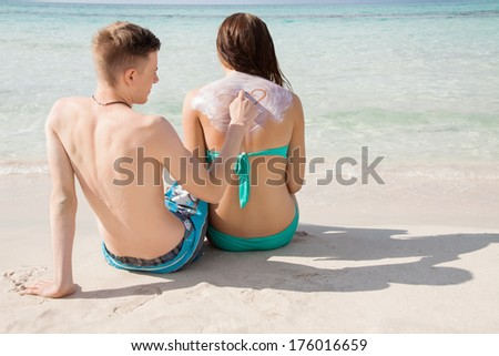 Romantic young man drawing a heart on his girlfriends back in a layer of sunscreen as they relax on the beach together sunbathing and enjoying a hot summers day - stock photo