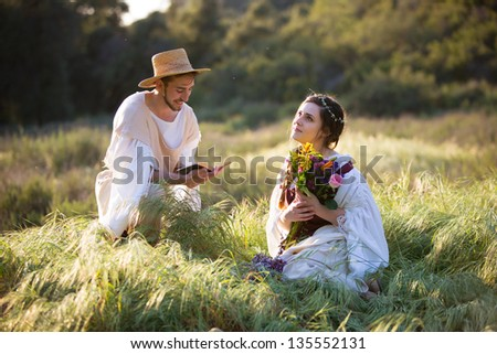 Romantic young man in historical clothing reads to a dreamy young woman with flowers - stock photo
