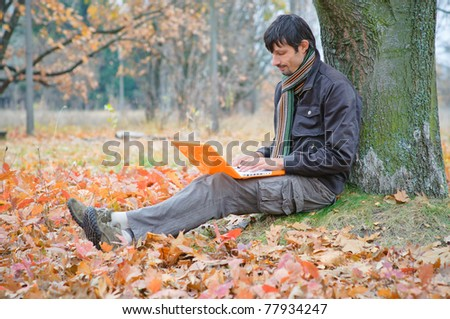 Romantic young man sitting with laptop in the autumn park. - stock photo