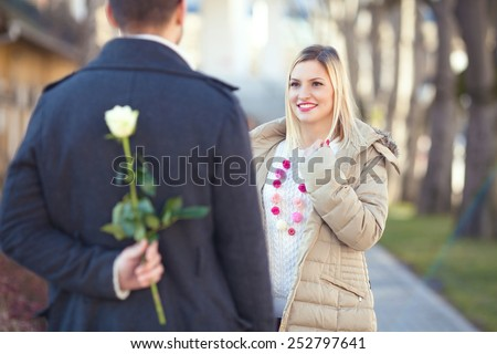 Romantic young man standing on the street  awaiting his girlfriend with a rose behind his back - stock photo