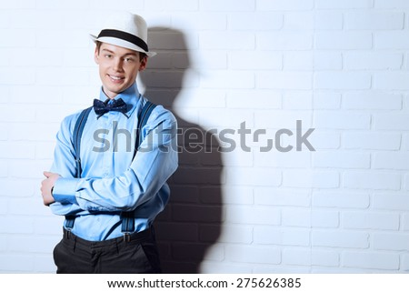 Romantic young man stands by the brick wall and smiling to camera. Men's beauty, fashion. - stock photo