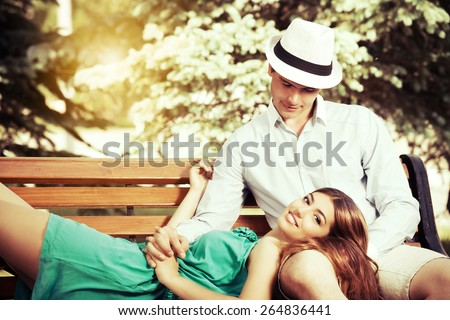 Romantic young people tenderly  talking on a park bench. Love concept. - stock photo