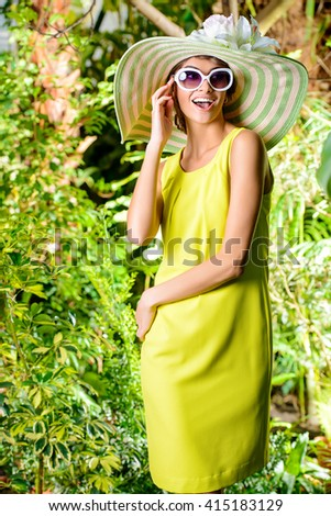Romantic young woman in a beautiful hat and sunglasses in a blooming garden. Beauty, fashion. - stock photo