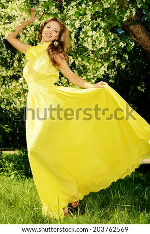 Romantic young woman in beautiful yellow dress on a green lawn in a blooming garden.  - stock photo