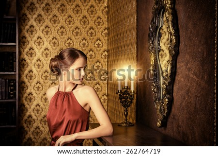 Romantic young woman in evening dress posing in vintage interior. Classic luxurious interior. Fashion shot. - stock photo