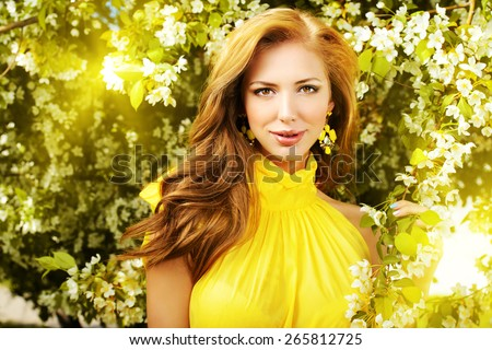 Romantic young woman in the spring garden among apple blossom.  - stock photo