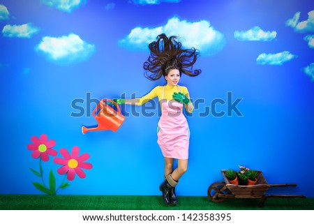 Romantic young woman is growing fabulous flowers. - stock photo