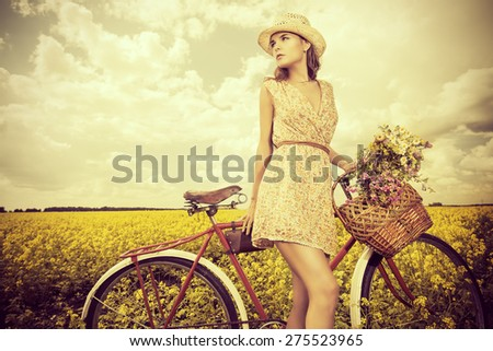 Romantic young woman stands in a field with her bicycle and a basket with wild flowers. Summer. - stock photo