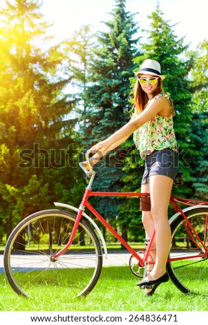 Romantic young woman  with beautiful smile rides a bicycle in a park. Summer day. - stock photo