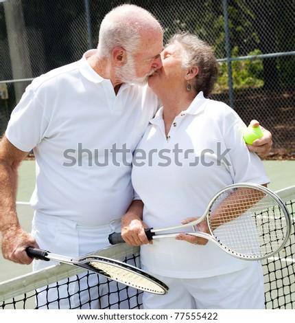 Romatic senior couple kissing on the tennis court. - stock photo