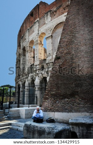 ROME - APRIL 29:Italian man work on his laptop outside the Colosseum on April 29 2011 in Rome Italy.All Ancient Romans had free entry to the Colosseum for events, and was also fed throughout the show. - stock photo