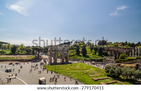 ROME - APRIL 17, 2013: Tourists walk next to The Arch of Constantine and Colosseum (Coliseum) and Forum Romanum on a sunny spring day with clear blue sky. View from Colosseum. Rome, Italy. - stock photo
