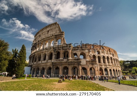 ROME - APRIL 17, 2013: Tourists walk next to The Colosseum or Coliseum, also known as the Flavian Amphitheatre on a sunny spring day. Flower bed in the foreground. Rome, Italy.