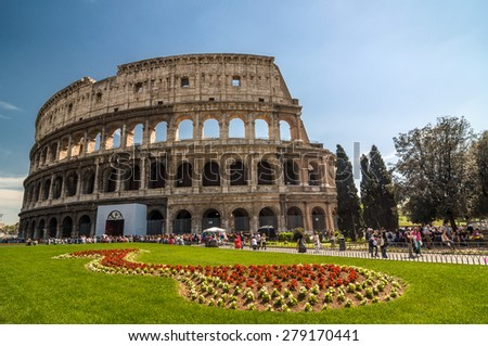 ROME - APRIL 17, 2013: Tourists walk next to The Colosseum or Coliseum, also known as the Flavian Amphitheatre on a sunny spring day. Flower bed in the foreground. Rome, Italy. - stock photo