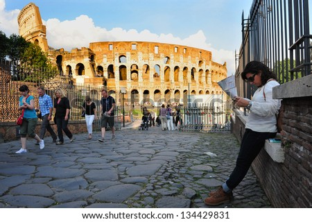 ROME - APRIL 29 2011:Visitors at the Colosseum in Rome Italy.Millions of people visit the Colosseum structure in hopes to get some sense to what it was like to live during the Ancient Roman times. - stock photo