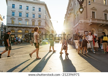 ROME - AUGUST 22: People walk on Via del Corso under a sun setting sky on August 22, 2014 in Rome, Italy. - stock photo