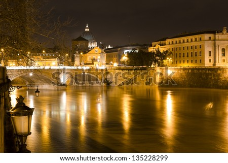 Rome by night. Tiber river, Vittorio Emanuele bridge and Dome of St. Peter in the Vatican city.