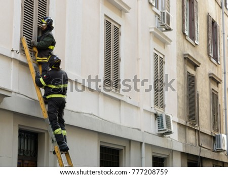 ROME, ITALY - DECEMBER 18, 2017: A rescue team of firefighters trying to enter in a home to rescue an elderly sick lady