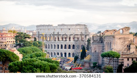ROME, ITALY - 1 December 2015: View of the Colosseum and some other ancient buildings being consolidated with lots of visitors around in this wonderful ancient destination
