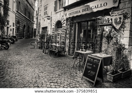 """ROME, ITALY, FEBRUARY 7, 2015: An old cobbled street in the heart of Rome with its traditional """"Osteria"""" type restaurants - stock photo"""