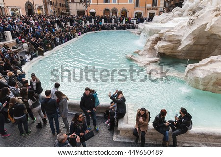 Rome, Italy - February 13, 2016: Many tourists visiting the Trevi Fountain an iconic symbol of Imperial Rome. It is one of the most popular tourist attractions in Rome - stock photo